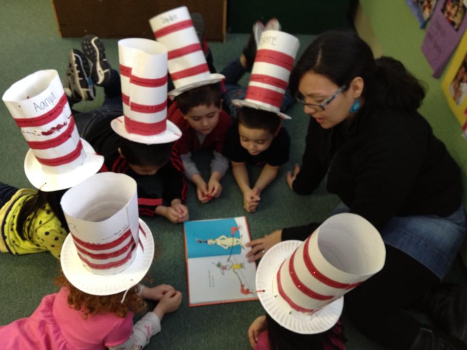 kids reading in the floor with Dr. Seuss hats